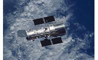 Teleskop Luar Angkasa Hubble dengan Bumi di latar belakang