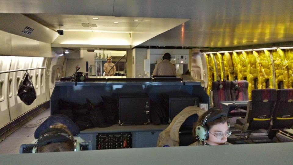 Interior of the plane in flight, facing forward, showing some of the flight crew