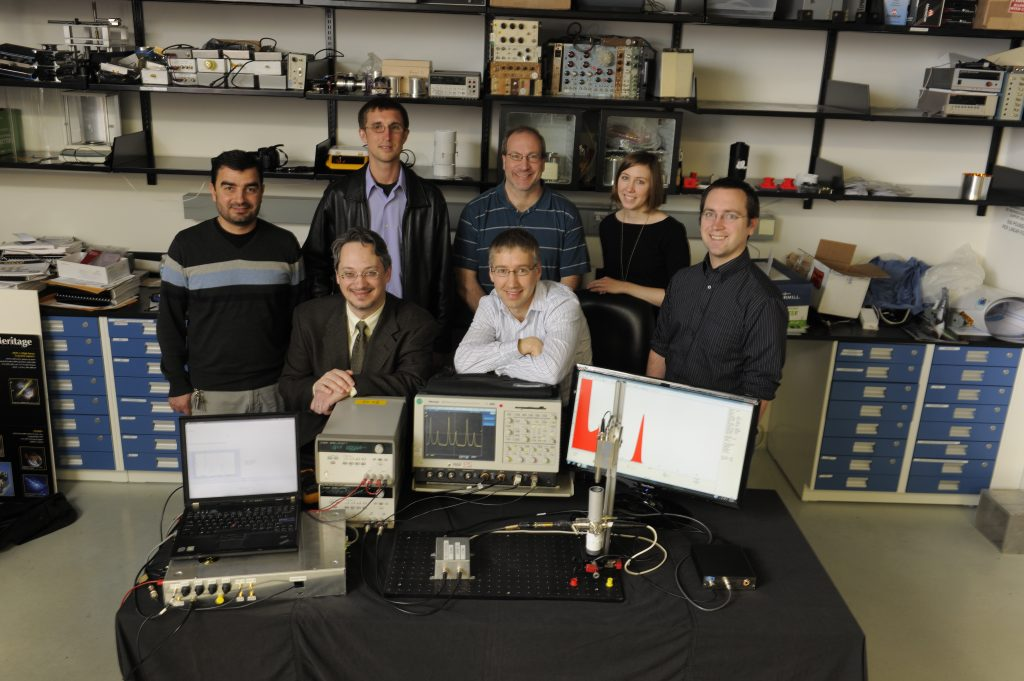 "Technologists at NASA's Goddard Space Flight Center in Greenbelt, Md., created what they believe is the world's first ""pulsar-on-a-table,"" a laboratory system shown here for testing emerging X-ray navigation technologies. Back row, left to right: Monther Hasouneh, John Gaebler, Harry Stello, Jennifer Valdez and Sam Price. Front row, left to right: Jason Mitchell and Luke Winternitz. Credits: NASA/ Pat Izzo"